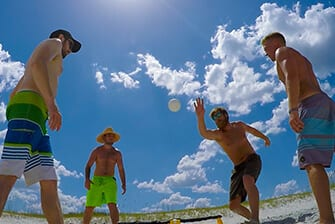 Four Men on the Beach Playing Catch