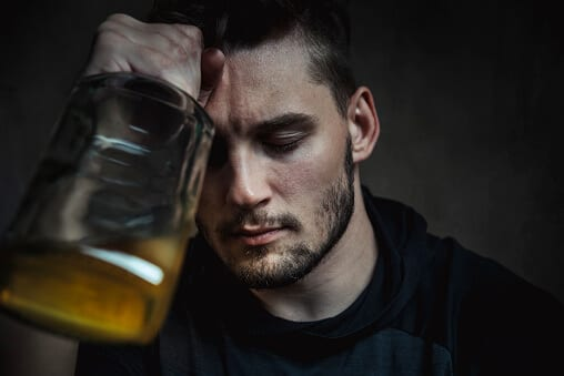Depressed man holding a bottle of alcohol against his head
