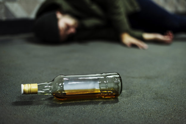 bottle of alcohol next to passed out man from drinking too much alcohol