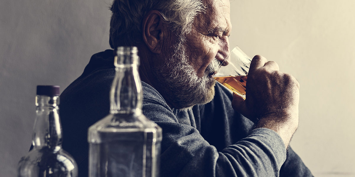 senior man sitting on floor heavy drinking in the stages of alcoholism