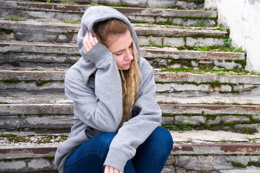 Young woman on steps feeling effects of drug withdrawal.