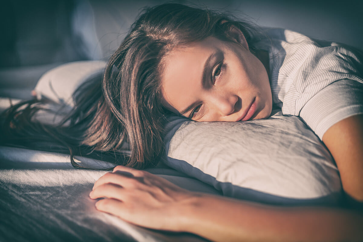 woman laying in bed wondering can you die from heroin withdrawal