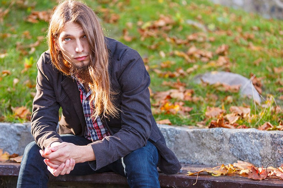 Young long haired man wondering about steroid addiction