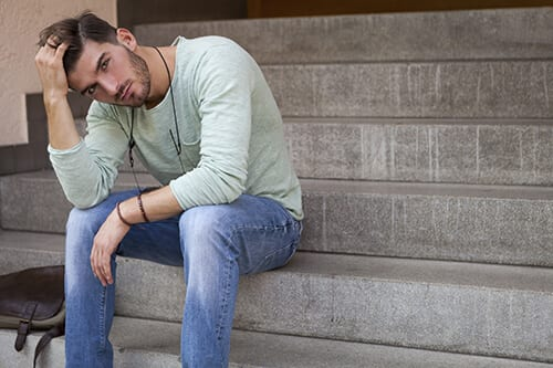 Disturbed young man on steps dealing with opioid addiction treatment
