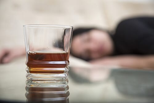 Passed out person in background showing lean drink side effects with lean drink in foreground.