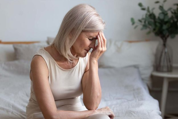 a woman puts her hand to her head as she considers the klonopin side effects