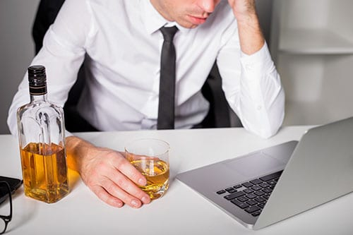 Man in tie drinking shows substance abuse in the workplace
