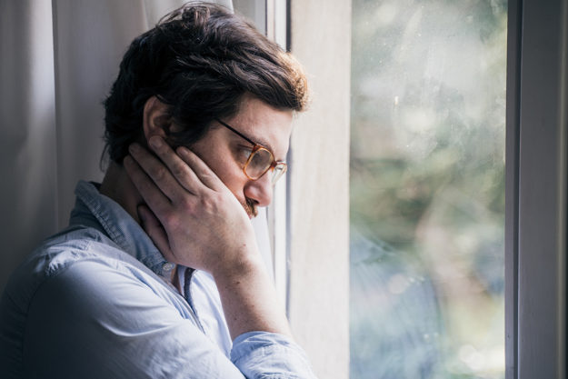 man looking out window concerned about how to fight drug cravings