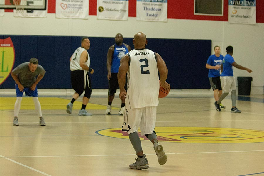 man dribbling at Beaches Recovery alumni program basketball game