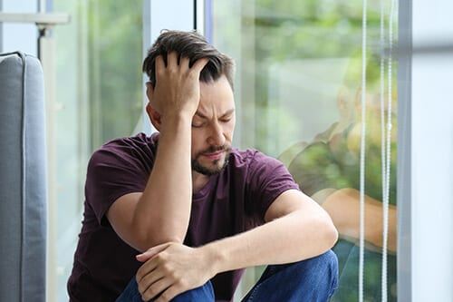 Visibly depressed man at window probably needs mood disorders treatment during addiction rehab