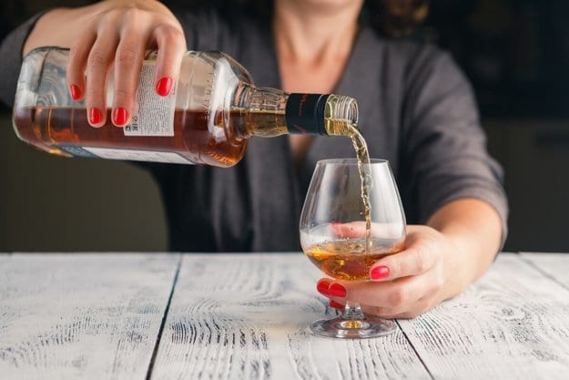 a person pours a drink ignoring Alcohol Awareness Month