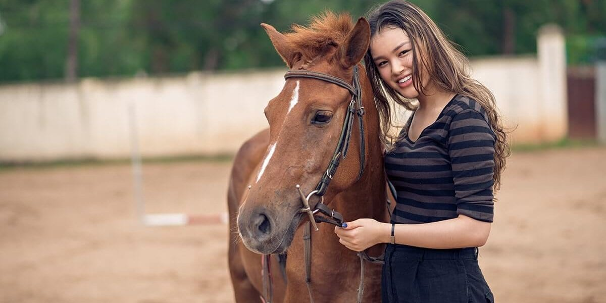 a woman smiles next to a horse thinking about the benefits of equine therapy