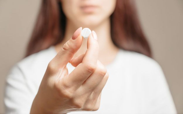 a woman holding a pill showing what are synthetic opioids