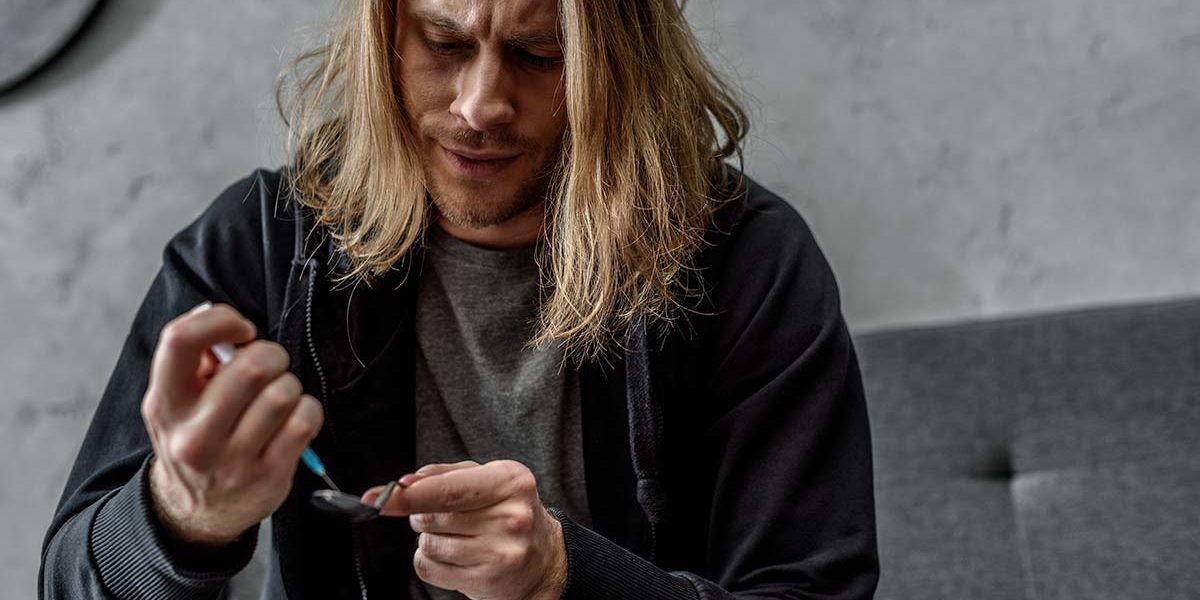man with heroin addiction using a syringe and spoon