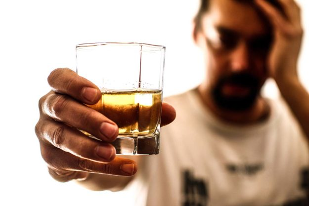 man passing back glass of alcohol ready to start treatment for alcohol addiction