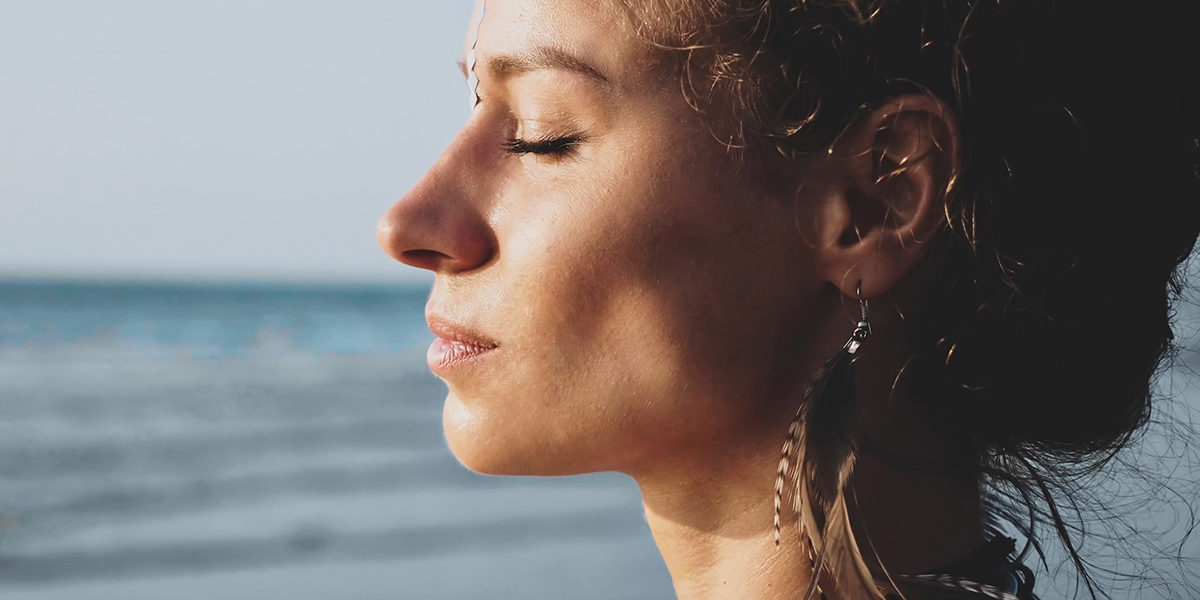 woman with eyes closed at the beach using techniques from Mindfulness Based Stress Reduction Therapy